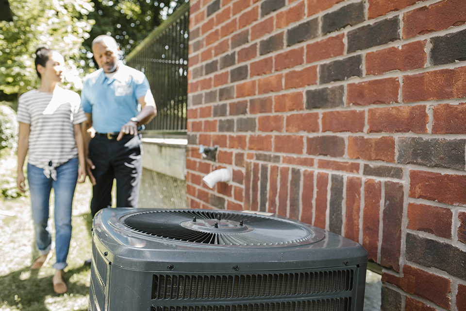 Homeowner and contractor walking together to air conditioner