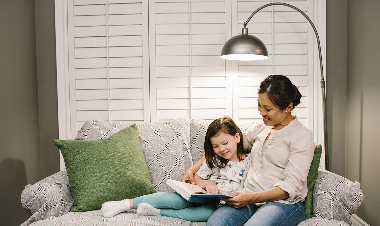 Mother reading to child under bright floor lamp in living room