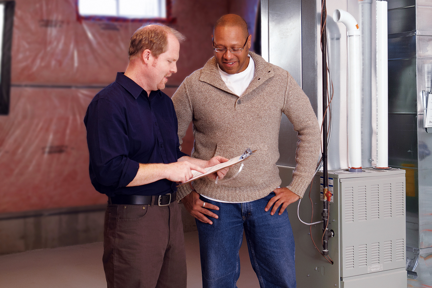 professional and resident having discussion in front of basement furnace