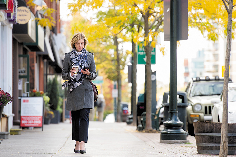 woman walking down the sidewalk on her cell phone